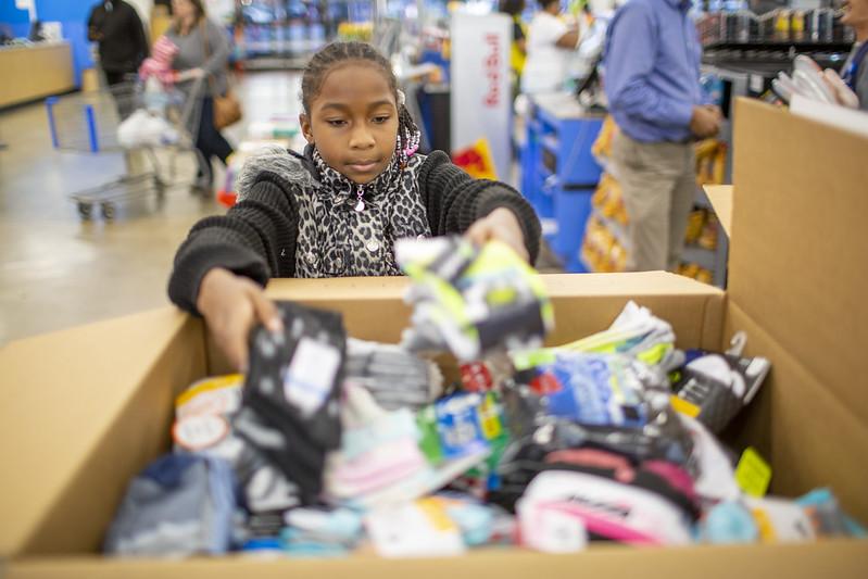 girl donates socks for socktober sock drive
