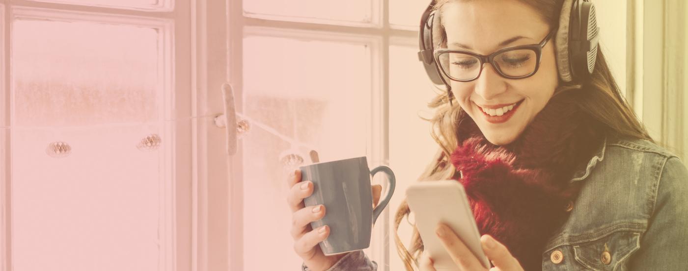 woman by window with headphones and mug